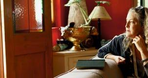 Bekymrat moget kvinnasammanträde på soffan i vardagsrum 4k arkivfilmer