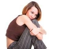 Bekymrat och rätt sammanträde för ung kvinna på stol. Isolerat arkivbilder
