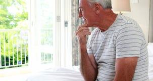 Bekymrat sammanträde för hög man på säng i sovrum arkivfilmer