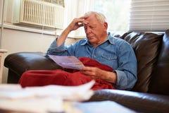 Bekymrat sammanträde för hög man på Sofa Looking At Bills Royaltyfri Foto