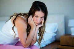 bekymrat seende kvinnasammanträde på hennes säng royaltyfria bilder