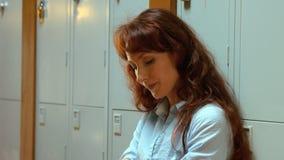 Bekymrat studentanseende vid hennes skåp lager videofilmer