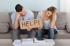 Bekymrat tecken för parinnehavhjälp, medan beräkna räkningar arkivfoto