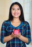 Belägen mitt emot kamera för ung brunettkvinna, hållande spargris och le lyckligt Royaltyfria Bilder