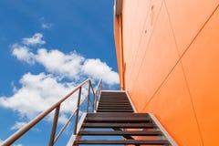 Belägga med metall brandflykten eller den nöd- utgången på den orange väggen av Buliding Royaltyfri Foto