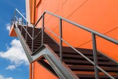 Belägga med metall brandflykten eller den nöd- utgången på den orange väggen av Buliding W Arkivbild