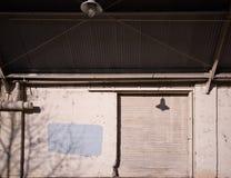 Belägga med metall dörren av ett gammalt lager med en markis Arkivfoto