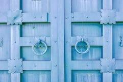 Belägga med metall den åldrades texturerade dörren för den bleka violeten med cirkeldörrhandtag och metalldetaljer i formen av st Royaltyfri Foto