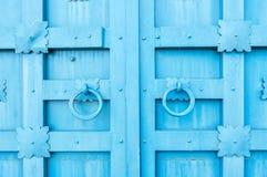 Belägga med metall den blåa åldriga texturerade dörren med cirkeldörrhandtag och metalldetaljer i formen av stiliserade blommor Royaltyfria Bilder