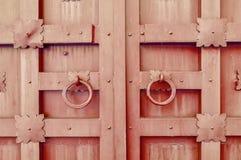 Belägga med metall den brun tappning texturerade dörren med cirkeldörrhandtag och metalldetaljer i formen av stiliserade blommor Arkivbild
