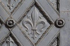 Belägga med metall den dekorativa dörren med korset och fleur de lis royaltyfri foto
