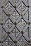 Belägga med metall den dekorativa dörren med korset och fleur de lis arkivfoto