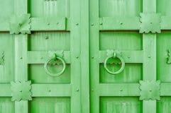Belägga med metall den gröna åldriga texturerade dörren med cirkeldörrhandtag och metalldetaljer i formen av stiliserade blommor Arkivfoton