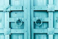 Belägga med metall den mörk turkos åldrades texturerade dörren med cirkeldörrhandtag och metalldetaljer i formen av stiliserade b Arkivfoto