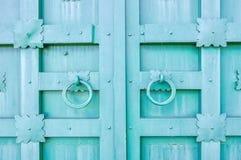 Belägga med metall den turkos åldrades texturerade dörren med cirkeldörrhandtag och metalldetaljer i formen av stiliserade blommo Arkivbilder