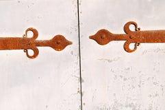 Belägga med metall den vit texturerade dörren med rostiga arkitektoniska detaljer som är fastnitade på den Royaltyfria Foton