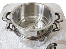Belägga med metall durkslaget och kastrullen för att laga mat på ånga Royaltyfri Foto
