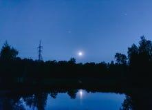 Belägga med metall elektriska poler i månskenet på sjön Royaltyfria Foton