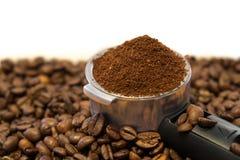 Belägga med metall hållaren med jordkaffe på kaffebönor Arkivbild