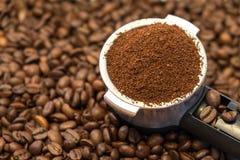 Belägga med metall hållaren med jordkaffe på kaffebönor Royaltyfri Bild