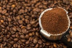 Belägga med metall hållaren med jordkaffe på kaffebönor Royaltyfria Foton