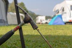 Belägga med metall hammaren som sätter a spika-som tältpinnen ut ur järn in i gräset royaltyfri bild