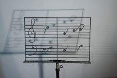 Belägga med metall hantverkaremusikställningen med utdragna musikaliska anmärkningar, med en skugga av personalen av musik Arkivbilder