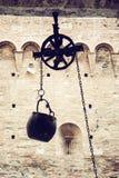 Belägga med metall hinken på ett block som hänger i borggården, gammalt filter Royaltyfri Bild