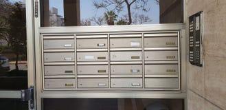 Belägga med metall individuella postaskar med lägenhetnummer royaltyfri foto