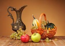 Belägga med metall kannan och frukt Arkivfoto
