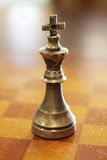 Belägga med metall konungschackstycket på ett träbräde Royaltyfria Bilder