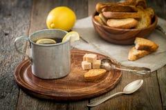Belägga med metall kopp te, farin, smällare och citronen royaltyfria bilder