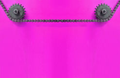 Belägga med metall kugghjul och kedja fast på purpurfärgad bakgrund med tomt utrymme Arkivbild