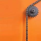 Belägga med metall kugghjulet och kedja fast på orange bakgrund med tomt utrymme Royaltyfri Bild