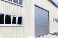 Belägga med metall lagerväggen med fönster och den stängda porten Arkivfoto