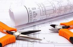 Belägga med metall plattång och det rullande elektriska diagrammet på byggnadsritning av huset fotografering för bildbyråer