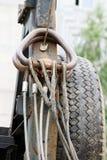 Belägga med metall rep som hänger på dess gångjärn bak taxin av gummihjul för en kranbakgrundssvart Arkivbild