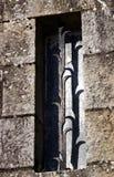 Belägga med metall spisgallret på ett blint fönster av en stenvägg Arkivbild