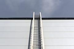 Belägga med metall stegen på den grå byggnadsväggen och himmel royaltyfri bild