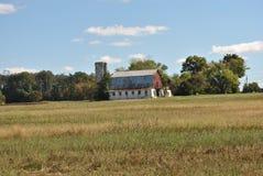 Belägga med metall taket av en ladugård i ett fält Arkivfoto