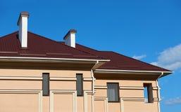 Belägga med metall taket och väggar av det nya privata huset, med lampglas och ventilation på bakgrunden av himmel, konstruktions royaltyfri foto