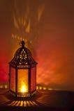 Belägga med metall tappninglyktabakgrund som tänds av levande ljus med djupt - röda och guldfärger Arkivfoton