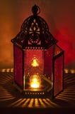 Belägga med metall tappninglyktan som tänds av levande ljus med djupt - röda och guldfärger Royaltyfri Foto