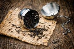 Belägga med metall teainfuser på trä bordlägger royaltyfria bilder