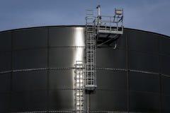 Belägga med metall trappa med en plattform på en stor rund behållare Fotografering för Bildbyråer