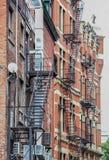 Belägga med metall trappa för brandflykten som hänger från sida av gammal tegelstenhyreshus Royaltyfri Fotografi