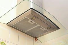 Belägga med metall utsugningsfläkten för spishuven med strålkastaren i lyxigt kök arkivfoto