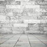 Belägga med tegel för stengolv och vit väggbakgrund Fotografering för Bildbyråer
