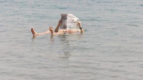 BELÉN, PALESTINA SEPTIEMBRE, 22, 2016: un hombre flota en el mar muerto de Israel y lee un periódico almacen de metraje de vídeo