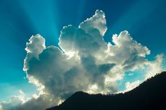 Bel éclat de lumière du soleil des nuages dans une montagne photos stock